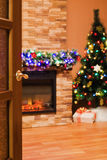 Room with an electric fireplace and a Christmas tree. Open the door to the room with an electric fireplace and a Christmas tree Royalty Free Stock Photos