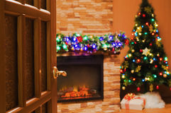Room with an electric fireplace and a Christmas tree. The view into the room with an electric fireplace and a Christmas tree through the open door Stock Images