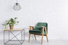 Room with brick wall. Room with empty white brick wall, green armchair and plant in copper pot stock image