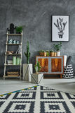 Room with ethnic dresser. Grey room with ethnic dresser, carpet and cactus royalty free stock images