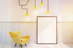 Room with a framed vertical poster and a yellow armchair, toned Stock Image