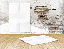 Room with hanging blank crumpled white poster at crack brick wal Stock Photography