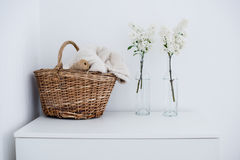 Room interior decoration. Wicker basket with home textiles and white lilac on a white chest, white vintage room interior decoration Royalty Free Stock Photo