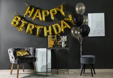 Room interior with gift boxes and phrase HAPPY BIRTHDAY made of balloon letters