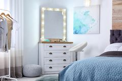 Room interior with makeup mirror, dressing table. And bed stock image
