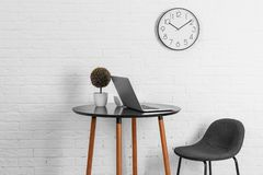 Room interior with table and analog clock hanging. On wall. Time of day stock image