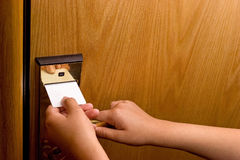 Room Key. A woman is unlocking the door with her room key Stock Image