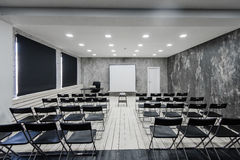 Room for lecture with a lot of dark chairs. Walls are white, loft interior. On the right there is a door. On the Royalty Free Stock Images