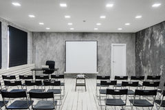 Room for lecture with a lot of dark chairs. Walls are white, loft interior. On the right there is a door. On the Stock Photo