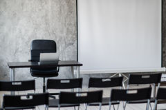 Room for lecture with a lot of dark chairs. Walls are white, loft interior. On the right there is a door. On the Royalty Free Stock Photography