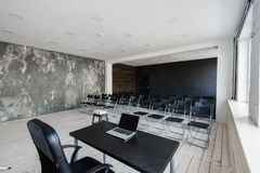 Room for lecture with a lot of dark chairs. Walls are white, loft interior. On the right there is a door. On the Stock Image