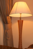 Room light. A wooden room light beside the window's curtain Stock Image