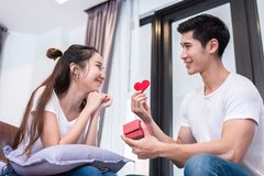 Room, living, young, happy, man, home, gift, couple, together, heart, box, surprise, sofa, people, female, person, girl, portrait. Man holding surprise box and stock images
