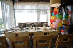 Room in a loft style in a restaurant. There are wooden tables with brown sofas and chairs. On the sofas there are color pillows Stock Photos