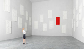 Room with many doors. Businesswoman standing in room with many white doors, one red, Concept of choice Stock Image
