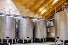 Wineries of La Rioja in Spain. Room with metal barrels to ferment wine with control windows, rules for liquid level vel and posters with the word danger, with a royalty free stock photos