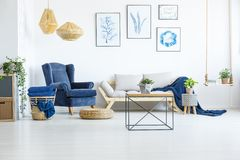 Room with navy blue armchair. White living room wih navy blue armchair, sofa and posters stock photo