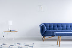 Room with navy blue couch. White lamp on table near geometric carpet in living room with navy blue couch and stool stock image