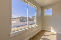 Room of a new house with a large window overlooking homes mountain and sky. Sunlight beams down on the carpeted floor on this sunny day stock photography