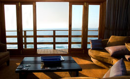 Room with ocean view. Comfortable lounge with ocean view bathed in golden morning light Royalty Free Stock Photos