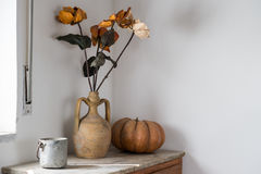 Room with old belief. With flowers, old bowl and pumpkin Stock Photo