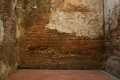 A room with an old red brick walls and disrepair. Stock Photos