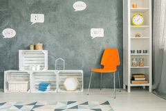Room with orange chair. Crate furniture and white regale stock image