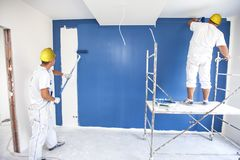 Room painter paints a wall in a new home. Unrecognizable Person Stock Photography