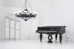 Room with a piano, folding screen and chandelier Royalty Free Stock Photo