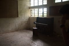 Room with piano in a old school ruin stock photo