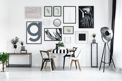 Table with modern chairs. Room with plants and wooden table with modern white and black chairs Royalty Free Stock Images