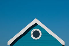 Room with a round view in blue. Porthole in blue beach hut gable looks out over the sea with deep blue summer sky stock photos