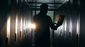 Room with servers and a silhouette of a male computer engineer stock video