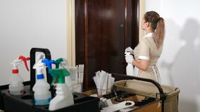 Room service concept. Back view on pretty young maid from hotel staff knocking at door. Shot through cleaning cart full