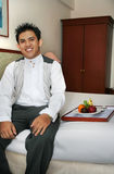 Room service in the hotel room. Waiter pose in the hotel room stock image