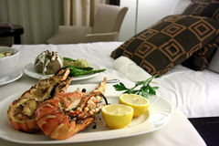 Room service lobster. Room service food presentation with hotel bed in background served lobster royalty free stock photography