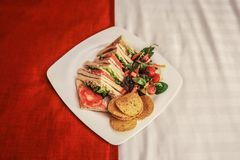 Room Service - Square plate with bacon tomato and lettuce sandwiches and chips and salad sitting on an attractively made up bed -. Closeup stock photography