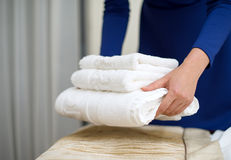 Room service. Woman changing towels in hotel room Royalty Free Stock Images
