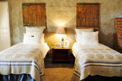 Room with single beds in guesthouse. French cottage style with brick walls and wooden headboards Stock Photography