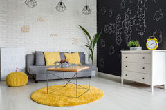 Room with sofa and dresser. Room with sofa, dresser, blackboard wall and yellow details royalty free stock images