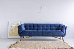Room with sofa and rug. Simple white room with blue sofa and rug Stock Photography