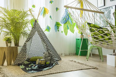 Room with tent and hammock. Child room with tent, hammock, rug and green houseplant stock images