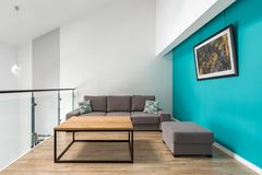 Small living room with turquoise wall. Small living room with gray sofa and pouf, wooden table and turquoise wall stock photo