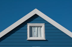 Room with a view on the beach. Blue beach hut roof with square window sits on the seashore with deep blue summer sky stock photography
