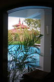 Room with a view of pool and architectured roofs through windo stock photos