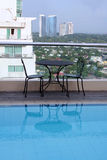 Room with a view rooftop swimming pool makati. Table and chairs beside rooftop swimming pool on roof of hotel Makati city in manila the philippines royalty free stock photo