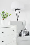 Room with white dresser. Armchair and floor lamp stock image