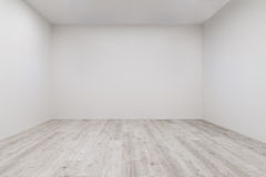 Room with whitewashed laminate and newly painted wall. Empty room with whitewashed floating laminate flooring and newly painted white wall in background royalty free stock photo