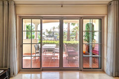 Room window with of the terrace and green gardens. Royalty Free Stock Photography