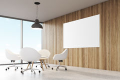 Room with wooden walls, large panoramic window a black ceiling lamp hanging above a coffee table Stock Photography